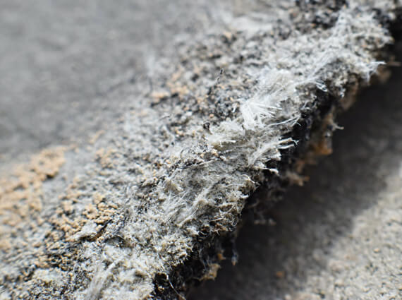 A close up picture of asbestos-infused construction material which is extremely dangerous to those who come in contact with it.