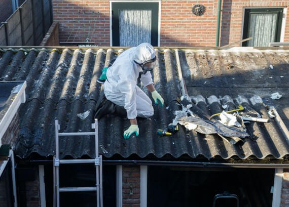 A first Response Cleaning Crew Member Removes Roof Tiles made With Asbestos