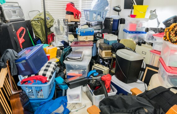 A room in a hoarder's house is cluttered with objects
