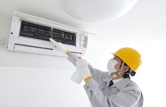 A First Response Cleaning Air Cleaning Specialist cleans and inspects an AC unit in an Ottawa home