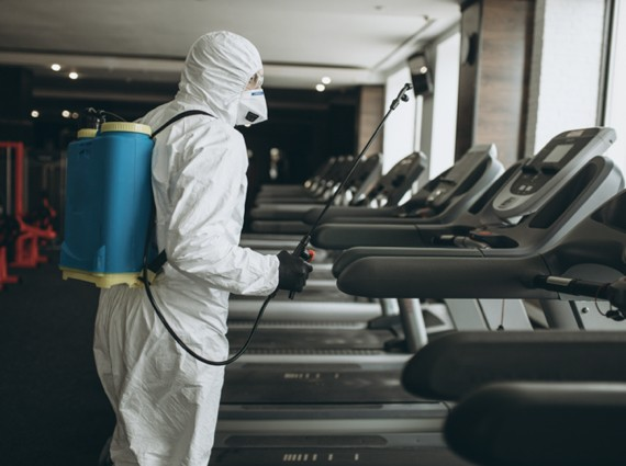 A First Response Cleaning crew member disinfects treadmills while wearing full PPE